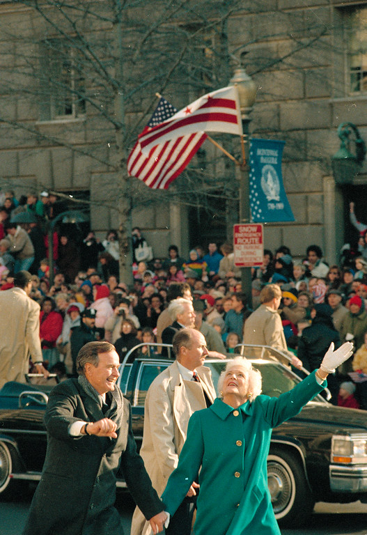 . President George Bush, left, and his wife, first lady Barbara Bush, wave to the crowd on Pennsylvania Avenue after getting out of their limousine and walking the inaugural parade route in Washington, D.C., Friday, Jan. 20, 1989.  Earlier, Bush was sworn in as the 41st president of the United States.  (AP Photo/Dennis Cook)