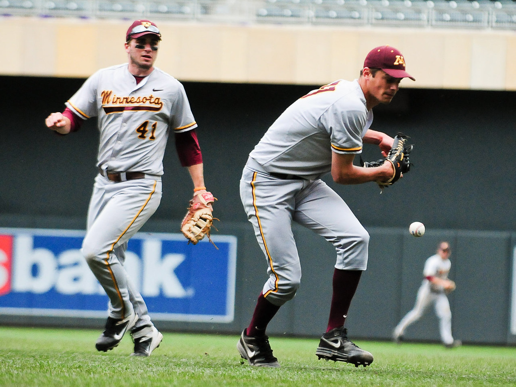 . Minnesota pitcher Dalton Sawyer fumbles the ball as he tries to throw to first in the fifth inning. At left is Dan Olinger. (Pioneer Press: Ben Garvin)