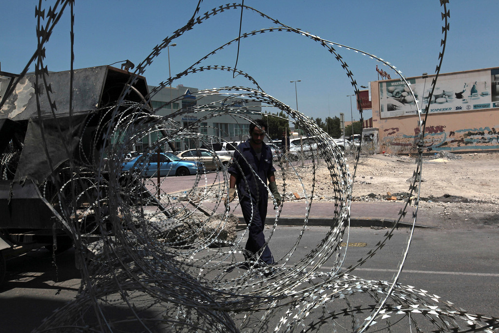 . A police employee walks behind razor wire being installed across a street between a village and main road on the outskirts of Manama, Bahrain, on Tuesday, Aug. 13, 2013. Bahraini authorities are stepping up security ahead of plans announced by the anti-government opposition to launch a major rebellion Wednesday against the Gulf monarchy. (AP Photo/Hasan Jamali)