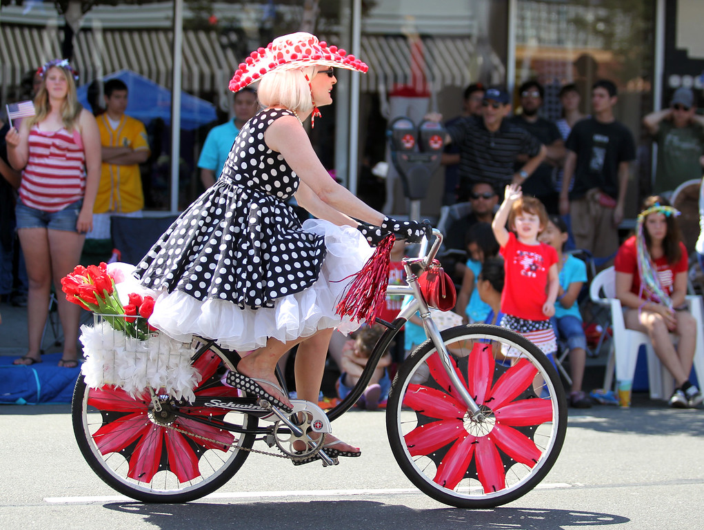 . A woman rides her decorated bicycle as she takes part in the Alameda Mayor\'s July 4th Parade on Park Street in Alameda, Calif., on Thursday, July 4, 2013. (Ray Chavez/Bay Area News Group)
