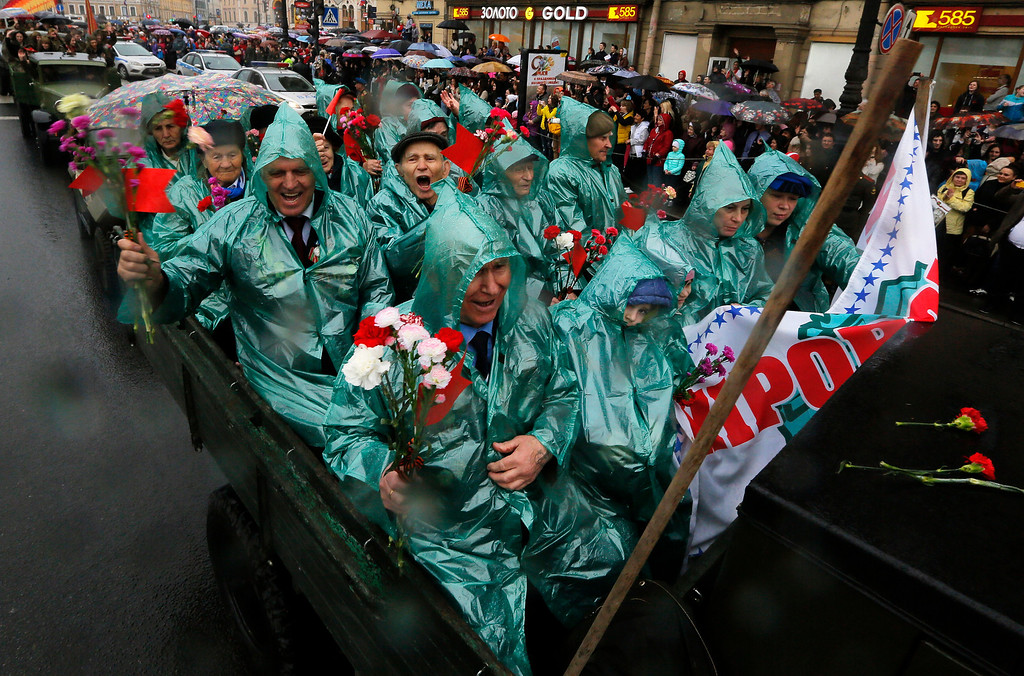 . World War II veterans and their relatives ride in the rain on a Soviet era vehicle during celebration of the Victory Day  in St.Petersburg, Russia, Friday, May 9, 2014. Victory Day, marking the defeat of Nazi Germany, is Russia\'s most important secular holiday celebrated on May 9. (AP Photo/Dmitry Lovetsky)