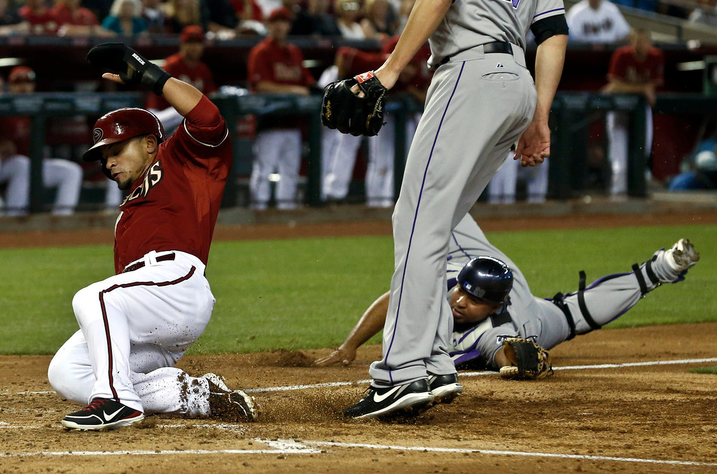 . Arizona Diamondbacks\' Gerardo Parra, left, avoids the tag of Colorado Rockies\' Wilin Rosario, right, and Rockies pitcher Jon Garland to score a run during the third inning of a baseball game, Sunday, April 28, 2013, in Phoenix. (AP Photo/Ross D. Franklin)