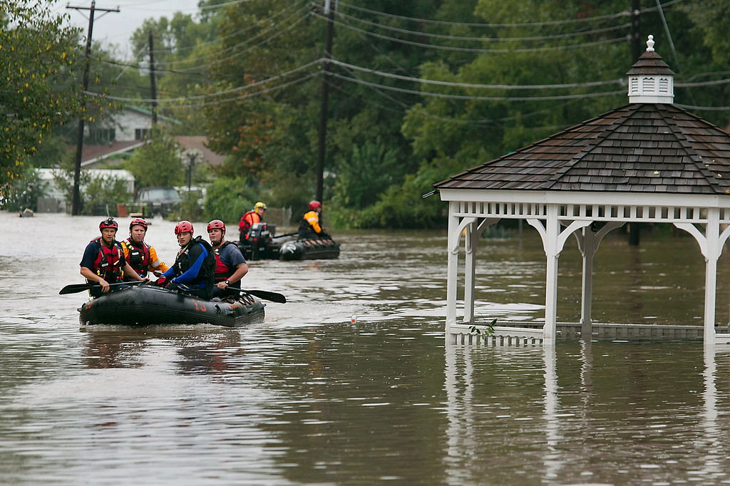 . Austin fire rescuers go through a neighborhood in search of anyone in need in Austin, Texas, on Thursday, Oct. 31, 2013. Heavy overnight rains brought flooding to the area. (AP Photo/Austin American-Statesman, Ralph Barrera)