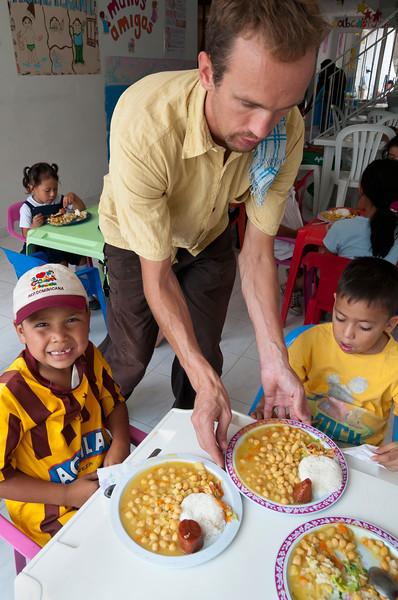Volunteer serves children a nutritious lunch.
