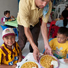 Volunteer serves children a nutritious lunch.