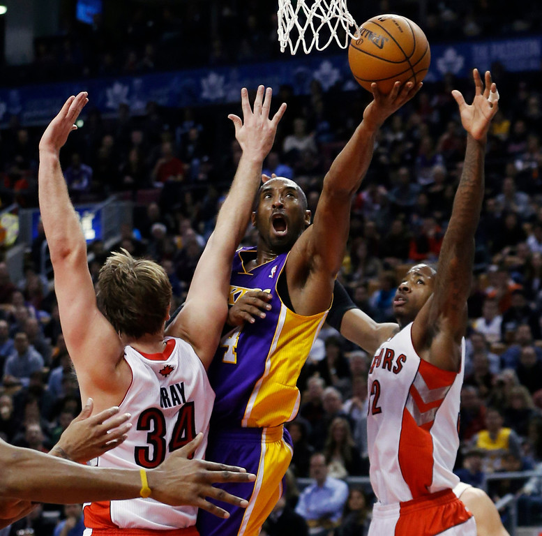. Los Angeles Lakers\' Kobe Bryant (C) goes to the basket against Toronto Raptors\' Aaron Gray (L) and Ed Davis during the first half of their NBA basketball game in Toronto, January 20, 2013.     REUTERS/Mark Blinch