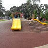 dual yellow plastic slides on mound with soft fall rubber and clambering boulders
