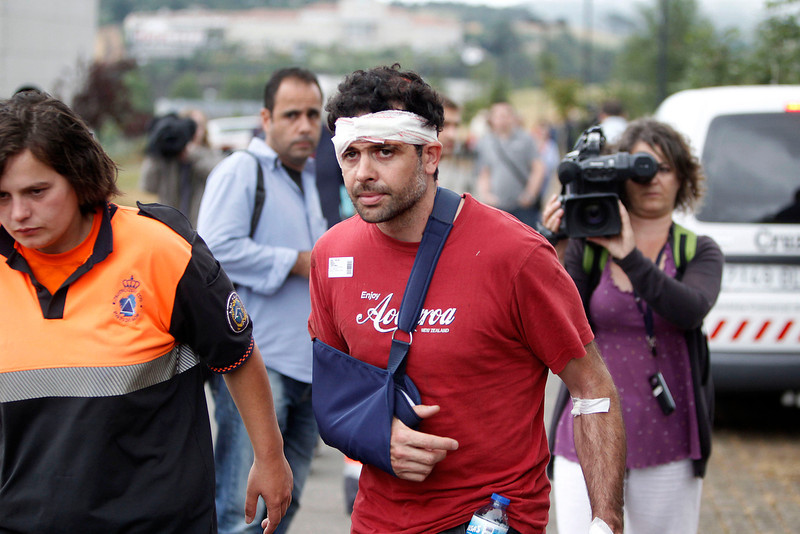 . A wounded man involved in a train accident arrives at a victims information point in Santiago de Compostela, Spain, on Thursday, July 25, 2013. The death toll in a passenger train crash in northwestern Spain rose to 77 Friday after the train jumped the tracks on a curvy stretch of track just before arriving in the northwestern shrine city of Santiago de Compostela, a judicial official said Thursday. (AP Photo/Salome Montes)
