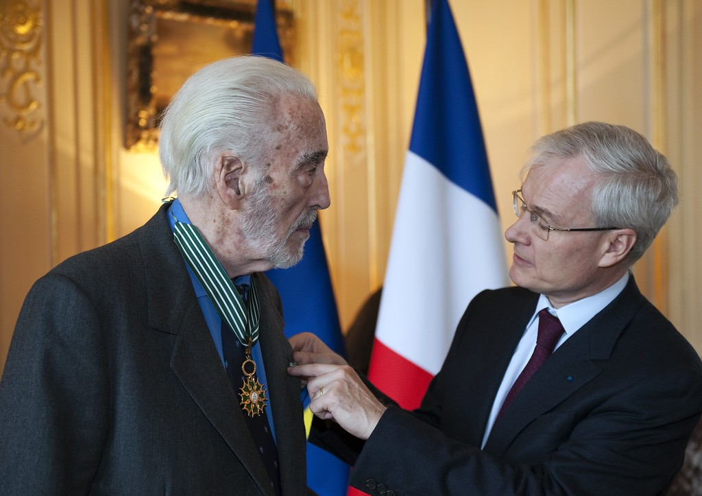 . French ambassador to Britain Bernard Emie (R) attaches a pin to the lapel of British actor Christopher Lee (L) after presenting him with the insignia of Commandeur de L\'Ordre des Arts et Lettres during a ceremony honoring Lee\'s contribution to the fields of art and literature at the ambassador\'s residence in London on December 16, 2011. Lee has performed roles in more than 275 films since 1947 and became famous for his role as Count Dracula in a string of Hammer Horror films. (ADRIAN DENNIS/AFP/Getty Images)