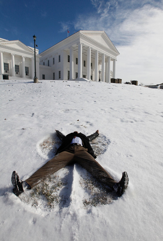 . Del. K. Rob Krupicka, D-Alexandria, makes a snow angel on  the front lawn of the Virginia State Capitol in Richmond, Va., Wednesday, Jan. 29, 2014.   (AP Photo/Richmond Times-Dispatch, Bob Brown).