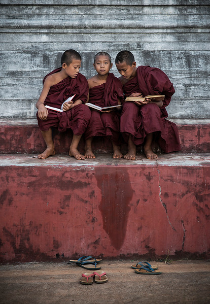 Three young monks reading in the temple grounds.  Pindaya, Myanmar, 2017