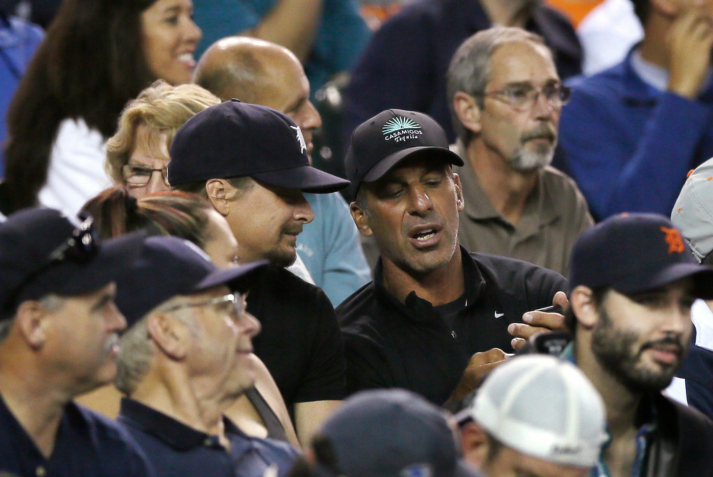 . Musician Kid Rock, center left, and former Detroit Red Wings Chris Chelios are seen during the fifth inning of a baseball game between the Detroit Tigers and the Chicago White Sox, Wednesday, July 30, 2014 in Detroit. (AP Photo/Carlos Osorio)