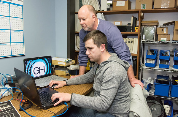 11/29/18 Wesley Bunnell | Staff CCSU Senior Szymon Szok, seated, works with manufacturing software while interning at the Gammons Hoagllund Company in Manchester as company President Paul Stefanik III looks over his work.