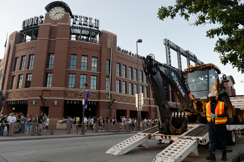 . DENVER, CO. - AUGUST 16:  A worker from Denver Water comes around a backhoe which will be used to fix a water main break along Blake St. out in front of Coors Field Saturday evening, August 16, 2014. The Rockies were set to play the Cincinnati Reds but the game was cancelled due to the water main break, which cut off water supply to the stadium. (Photo By Andy Cross / The Denver Post)
