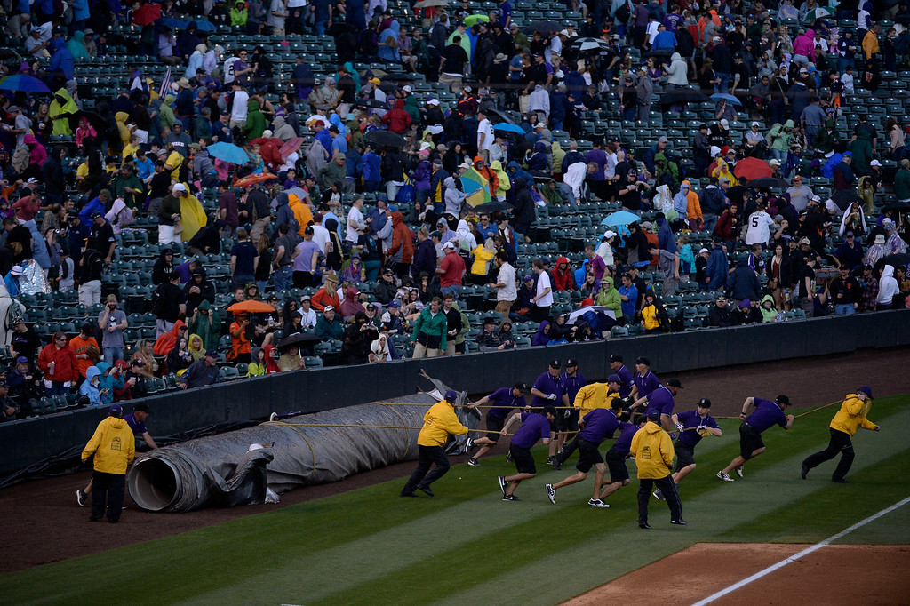 . DENVER, CO - MAY 22: Colorado Rockies grounds crew roles out the tarp to cover the field as rains begins to fall during their game agains the  San Francisco Giants May 22, 2014 at Coors Field. (Photo by John Leyba/The Denver Post)