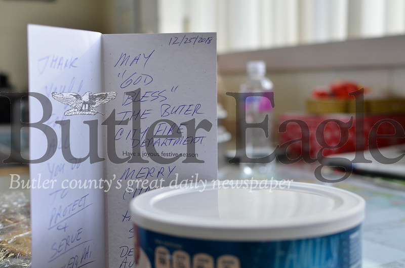 A holiday card sent by Denny Offstein sat among gifts at the Butler Bureau of Fire Tuesday. Tanner Cole/Butler Eagle