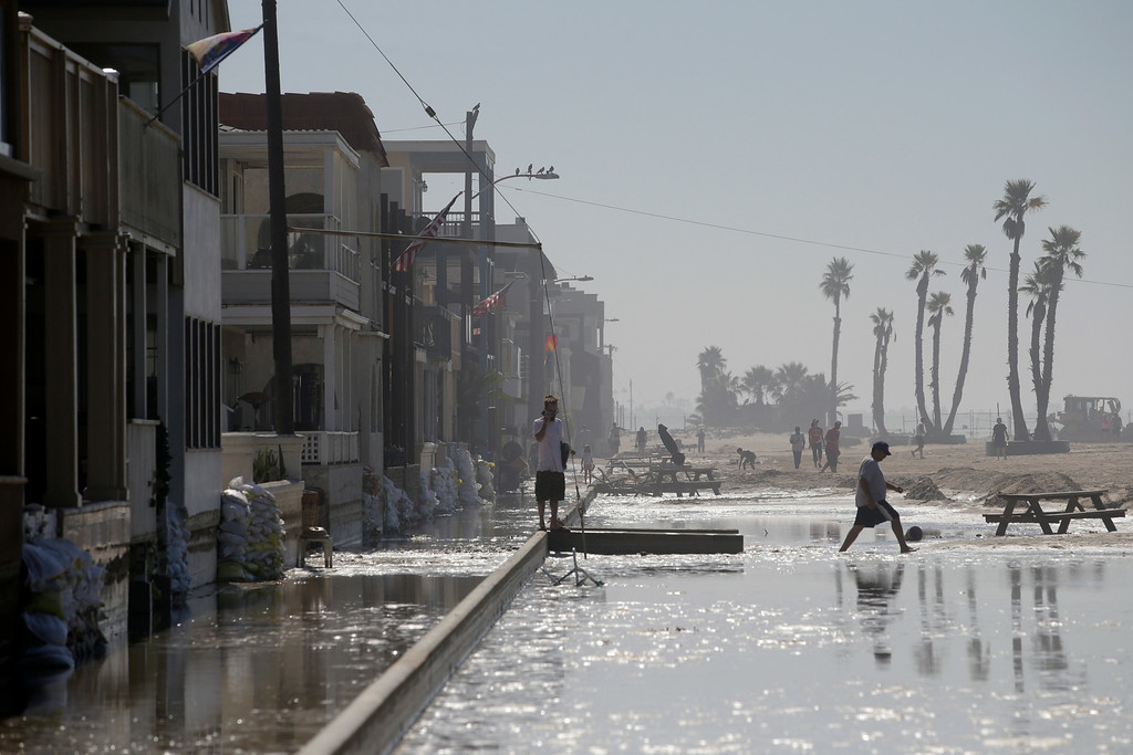 . A man walks through the flooded beachfront properties on Wednesday, Aug. 27, 2014, in Seal Beach, Calif. A low-lying street in the Southern California coastal community of Seal Beach has been inundated by a surge of rising seawater brought on by Hurricane Marie spinning off Mexico\'s Pacific coast. (AP Photo/Jae C. Hong)