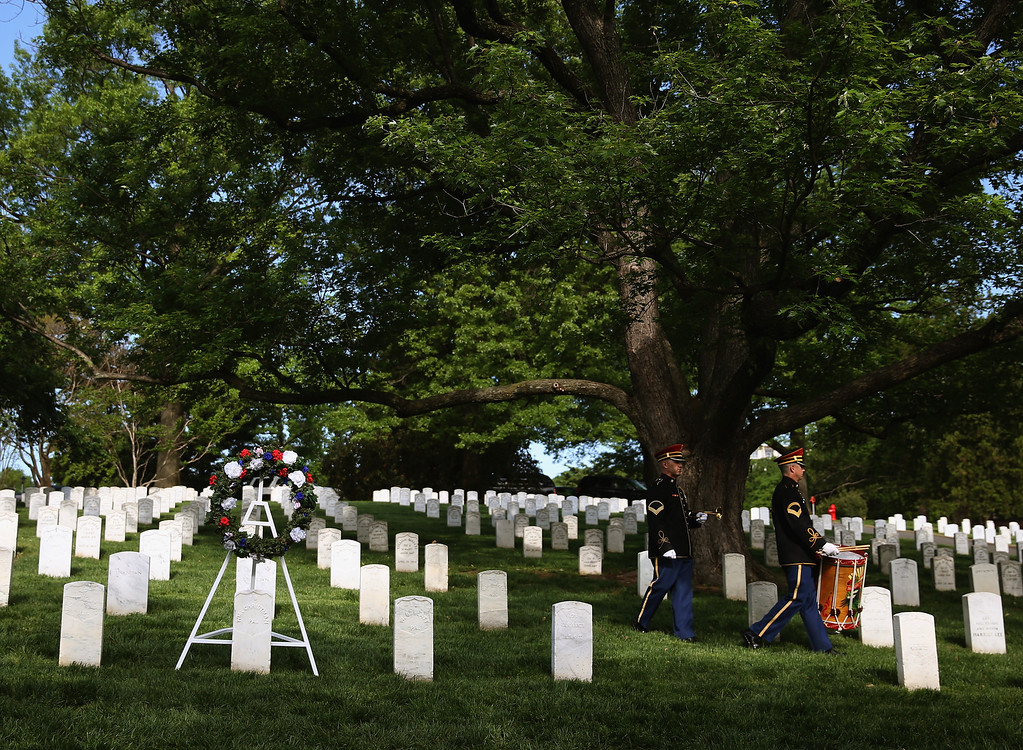 . A U.S. Military bugler and drummer walk away from the grave of Army Pvt. William Christman, after a wreath laying ceremony as part of Arlington at 150 Celebration on May 13, 2014 in Washington, DC.   (Photo by Mark Wilson/Getty Images)
