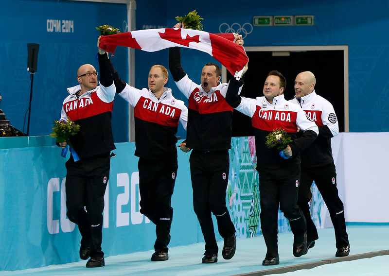 . Canadian curlers, from left,  Ryan Harnden, Brad Jacobs, E.J. Harnden, Caleb Flaxey, and Ryan Fry, take a lap around the ice after defeating Britain in the men\'s curling gold medal game at the 2014 Winter Olympics, Friday, Feb. 21, 2014, in Sochi, Russia. (AP Photo/Robert F. Bukaty)