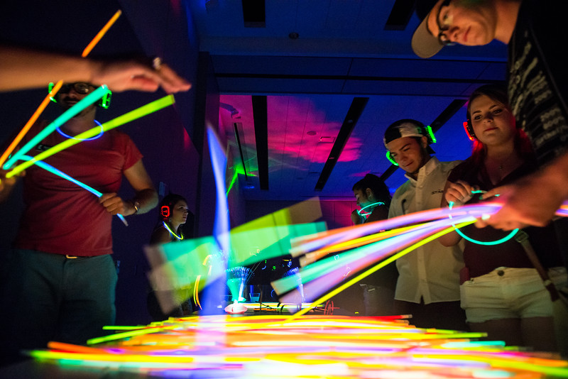 Students help themselves to some glow sticks for the NSO Glow Party in the UC Anchor Ballroom.
