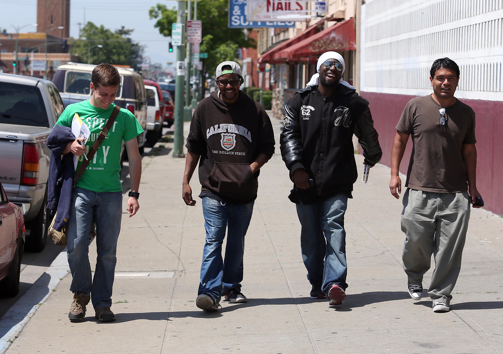 . John Burns, of the Urban Church, left, walks with church volunteers Vernon Byrd, Jaron Isom, and head pastor Ron Nunez, all of Oakland, left to right, as they pass out flyers and neighborhood surveys along International Boulevard near Seminary Avenue in Oakland, Calif., on Friday, April 26, 2013.  They are working in hopes of helping to reduce the violence in the neighborhood. (Jane Tyska/Staff)