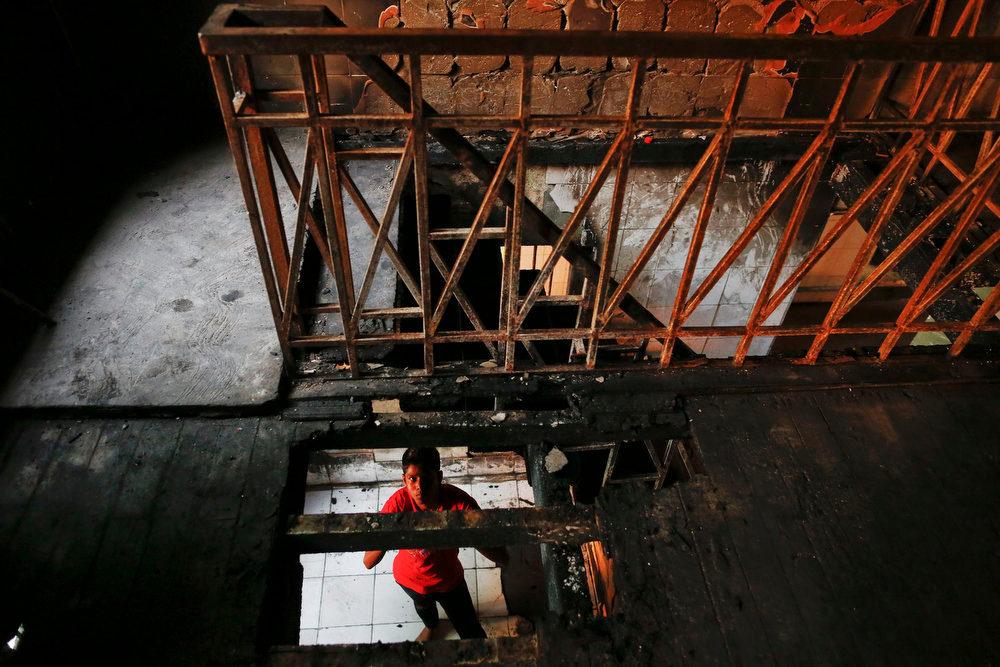 . A man looks up at the room of the Islamic school where 13 boys were killed by a fire in the central, multi-ethnic Botataung district of the former capital Yangon on April 3, 2013. Security has been tightened in parts of Myanmar\'s biggest city and former capital Yangon after the fire caused by faulty electrical equipment killed 13 boys in the dormitory of the school on Tuesday. REUTERS/Damir Sagolj