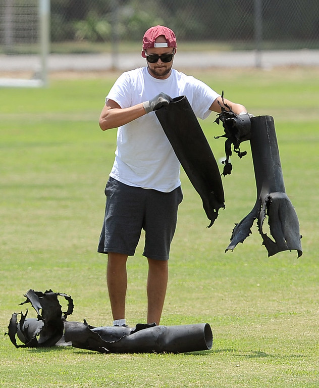 . A worker picks up debris from a fireworks show accident which injured 28 people at Rancho Santa Susana Community Park in Simi Valley, CA July 5, 2013.     (Andy Holzman/Los Angeles Daily News)