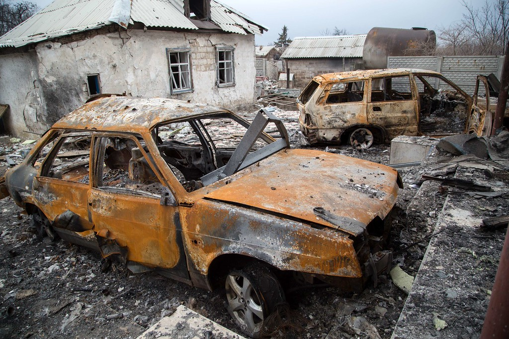 ". Burnt out vehicles are strewn next to a destroyed building in Pisky village, in the eastern Donetsk region, controlled by Ukrainian froces on February 26, 2015. Ukraine\'s military said Thursday it was starting the withdrawal of heavy weapons from the frontline with pro-Russian rebels, a key step in a stuttering peace plan. ""Ukraine is today (Thursday) beginning the withdrawal of 100mm cannons from the frontline. This is the first step in the pull-back of heavy weapons,\"" the military said in a statement. OLEKSANDR RATUSHNIAK/AFP/Getty Images"