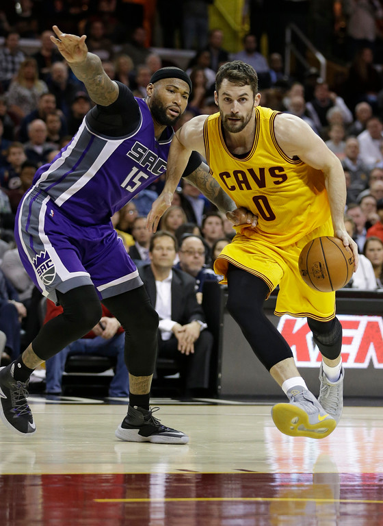 . Cleveland Cavaliers\' Kevin Love (0) drives against Sacramento Kings\' DeMarcus Cousins (15) in the second half of an NBA basketball game, Wednesday, Jan. 25, 2017, in Cleveland. (AP Photo/Tony Dejak)