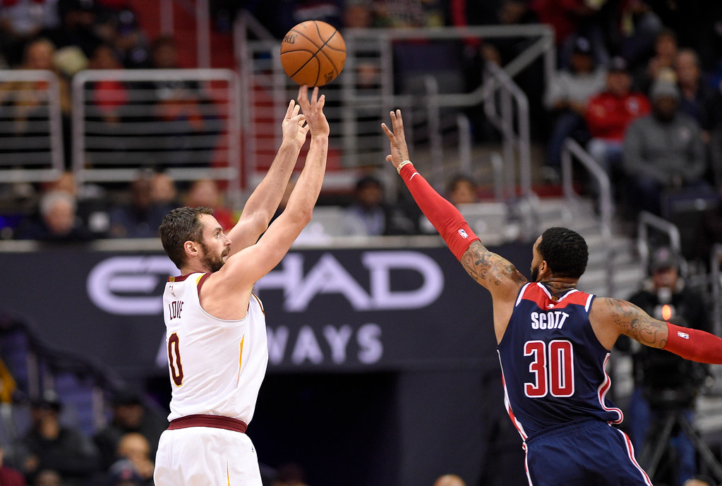 . Cleveland Cavaliers forward Kevin Love (0) shoots against Washington Wizards forward Mike Scott (30) during the second half of an NBA basketball game, Sunday, Dec. 17, 2017, in Washington. The Cavaliers won 106-99. (AP Photo/Nick Wass)