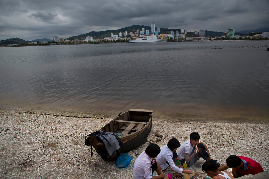 """. In this June 21, 2014 photo, a group of young North Koreans enjoys a picnic on the beach in Wonsan, North Korea. The Associated Press was granted permission to embark on a weeklong road trip across North Korea to the countryís spiritual summit Mount Paektu. The trip was on North Korea\'s terms.  AP reporter and photographer couldn\'t interview ordinary people or wander off course, and government \""""minders\"""" accompanied them the entire way. (AP Photo/David Guttenfelder)"""