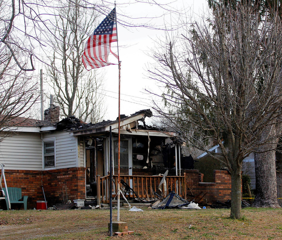 . A U.S. flag flies near the charred remains of a home Sunday, March 10, 2013, in Gray, Ky., where a fire erupted Saturday, killing two adults and five children inside. (AP Photo/Lisa Norman-Hudson)
