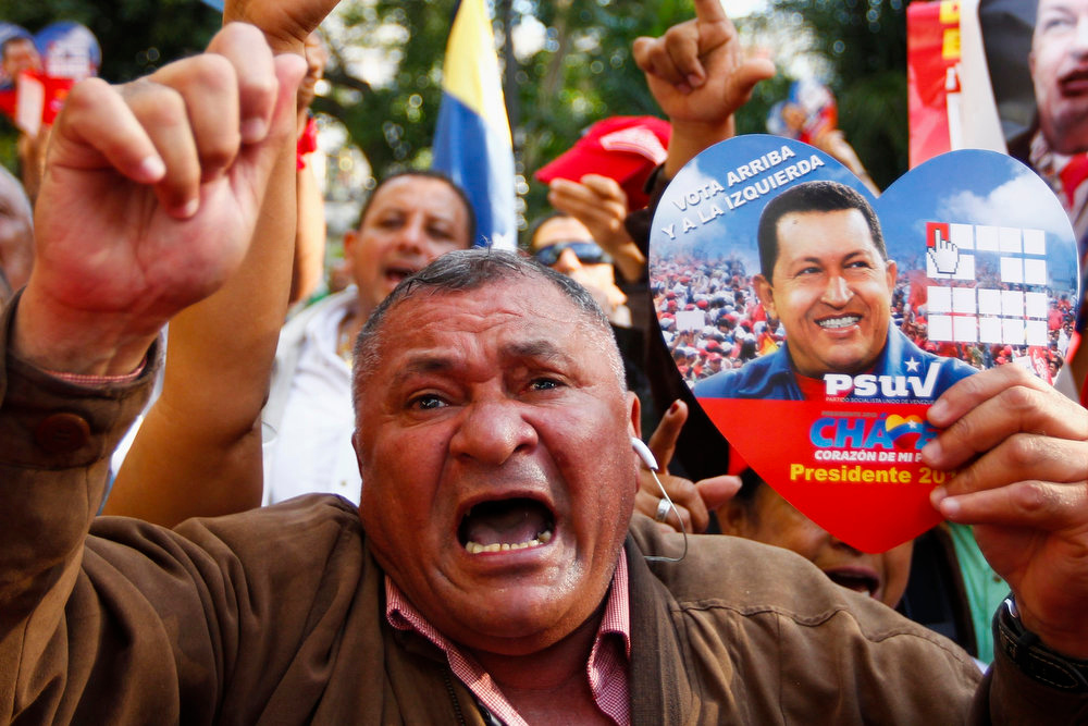 Description of . A supporter of Venezuelan President Hugo Chavez takes part in a gathering at Plaza Bolivar in Caracas February 18, 2013. Chavez made a surprise return from Cuba on Monday more than two months after surgery for cancer that has jeopardized his 14-year rule of the South American OPEC member. The 58-year-old socialist leader underwent a six-hour operation in Cuba on December 11. He had not been seen or heard in public since then until photos were published of him on Friday. REUTERS/Carlos Garcia Rawlins