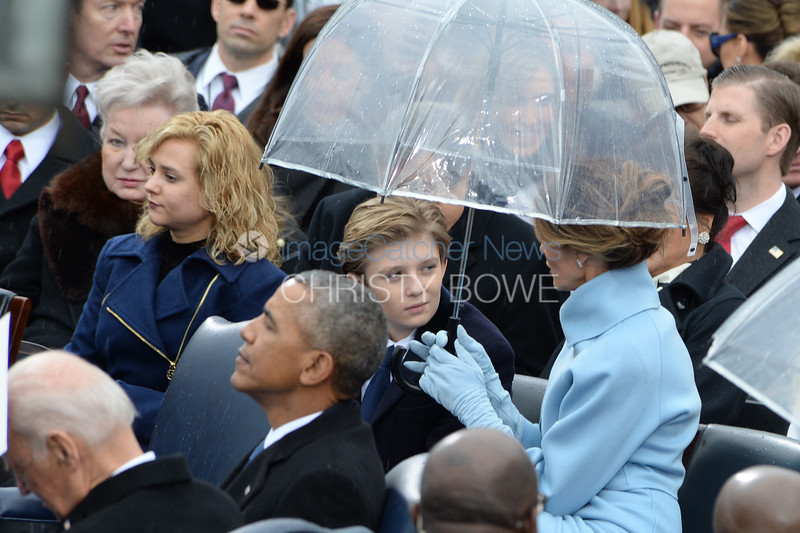 First Lady Melania holds an umbrella over herself and son Barron while her husband makes his Inaugural address.
