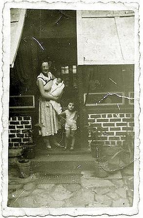 """1956 Teresa Adalberto, com  filhos: Beka ao colo e Zelinha numa casa antiga de Andrada ( janelas com rede e painel aberto com um """"mutondo"""")"""
