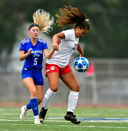 9/12/2019 Mike Orazzi | StaffrConard High School's Maddy Hoang (32) and Plainville's Skyler Ibitz (5) on Thursday.
