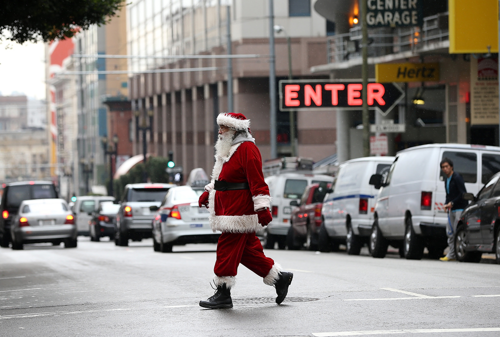 Description of . A man dressed as Santa Claus walks down Geary Street on December 14, 2012 in San Francisco, California.  With less than two weeks before Christmas, San Franciscans are getting into the holiday spirit. (Photo by Justin Sullivan/Getty Images)