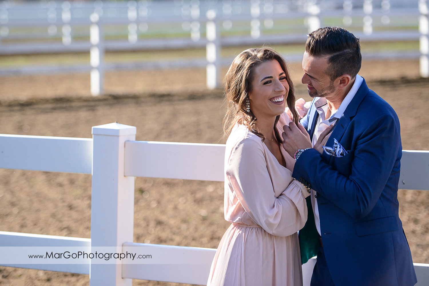 man in blue suit looking with love at woman in pink dress during Napa Valley engagement session at Tamber Bey Vineyards in Calistoga