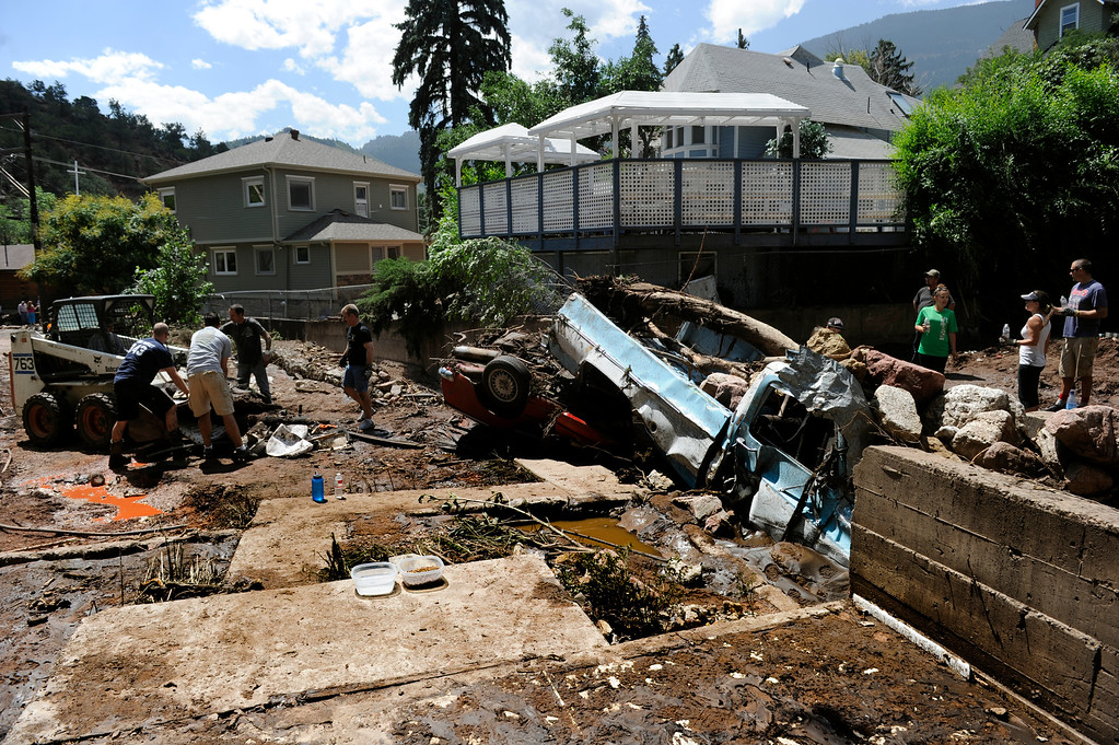 . MANITOU SPRINGS, CO - Aug.10: Looking across the foundation where one house once stood but was washed away with flood waters, residents and crews clean up the damage and debris along Canon Avenue after a flash flood roared through the streets and hillsides on Friday evening. (Photo By Kathryn Scott Osler/The Denver Post)