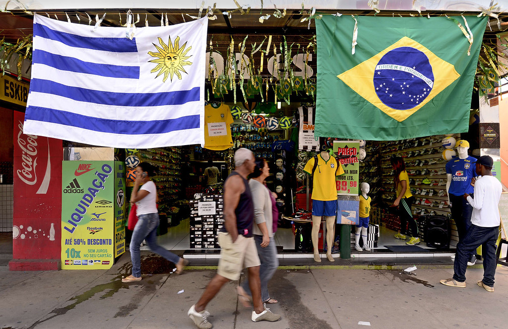 . Pedestrians walk past Uruguayan and Brazilian flags hanging at the entrance of a sports shop in Sete Lagoas some 50kms north of Belo Horizonte on June 10, 2014, three days before the start of the 2014 FIFA World Cup.     AFP PHOTO / DANIEL GARCIA/AFP/Getty Images