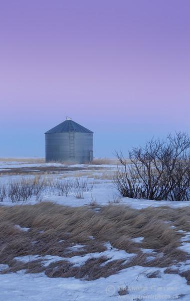 Grain bin in a snow-covered field at dusk. Elrose, Saskatchewan