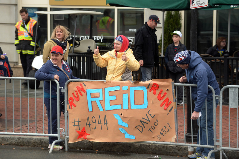 . People hang signs in Kenmore Square as they wait for runners as the Boston Marathon gets underway April 20, 2015 in Boston, Massachusetts. This is the 119th running of the Boston Marathon. Photo by Darren McCollester/Getty Images)
