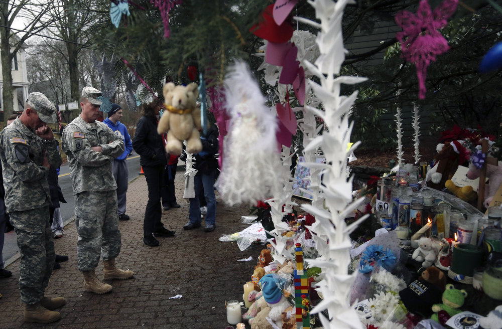 Description of . Soldiers pay their respects at one of the makeshift memorials for the Sandy Hook elementary shooting, Monday,Dec. 17, 2012 in Newtown, Conn. Authorities say a gunman killed his mother at their home and then opened fire inside the Sandy Hook Elementary School in Newtown, killing 26 people, including 20 children, before taking his own life, on Friday. (AP Photo/Mary Altaffer)