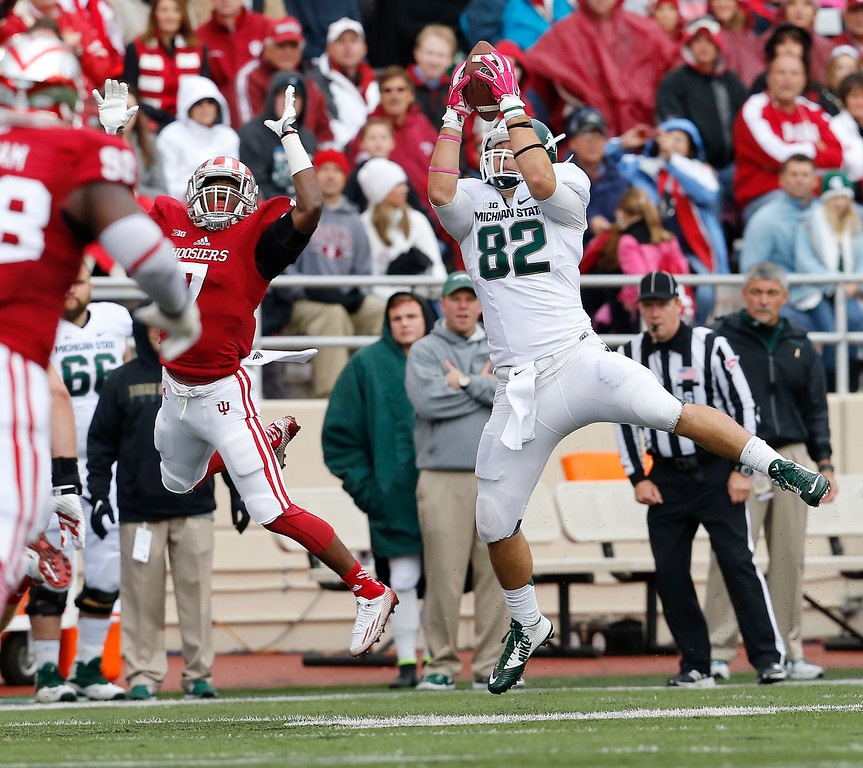 . Michigan State tight end Josiah Price (82) hauls in a pass against Indiana in the first half of an NCAA college football game in Bloomington, Ind., Saturday, Oct. 18, 2014. (AP Photo/Sam Riche)