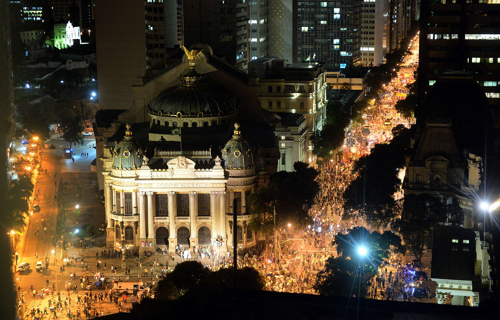 ". Aerial view of the clashes happening in front of the Municipal Theatre in Rio de Janeiro on July 11, 2013 after a march by Brazilian workers in a day of industrial action called by major unions to press demands for better work conditions. Demonstrators on Thursday blocked roads and staged protest rallies across the country on the ""National Day of Struggles\"" which was called by the country\'s five leading labour federations during last month\'s mass street protests to demand better public services and an end to endemic corruption. TASSO MARCELO/AFP/Getty Images"