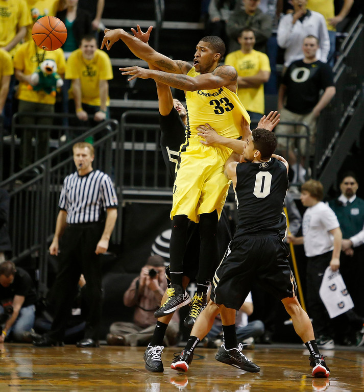 . Oregon\'s Carlos Emory gets off a pass as Colorado\'s Askia Booker (0) and Andre Roberson, rear,  converge during the first half of Colorado\'s game against Oregon in an NCAA college basketball game at Matthew Knight Arena in Eugene, Ore. Thursday, Feb. 7, 2013. (AP Photo/Brian Davies)