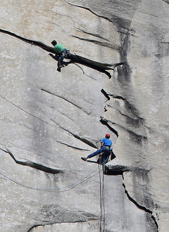 """. Kevin Jorgeson of California, wearing green, and 36-year-old Tommy Caldwell, wearing blue, near the summit of El Capitan Wednesday, Jan. 14, 2015, as seen from the valley floor in Yosemite National Park, Calif. The two climbers vying to become the first in the world to use only their hands and feet to scale a sheer granite face in California\'s Yosemite National Park are almost to the top. Jorgeson and Caldwell have been attempting what many thought impossible. The men have been \""""free-climbing\"""" to the 3,000-foot summit for 17 days, meaning they don\'t use climbing aids other than ropes only to prevent deadly falls. Each trained for more than five years, and they have battled bloodied fingers and unseasonably warm weather. (AP Photo/Ben Margot)"""