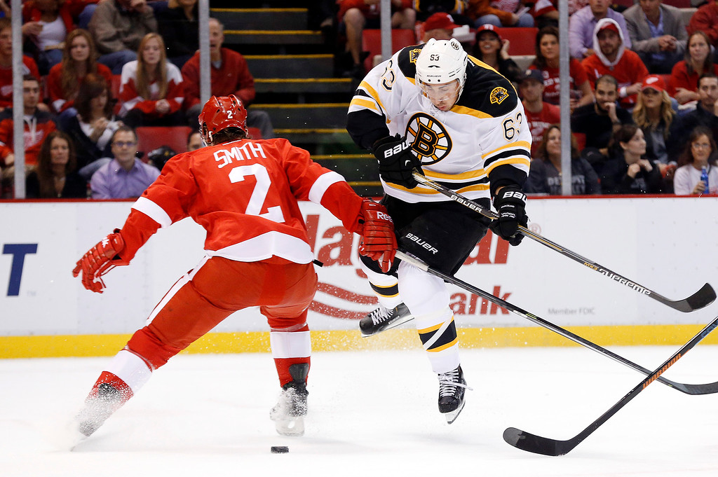 . Boston Bruins left wing Brad Marchand (63) jumps to get around Detroit Red Wings defenseman Brendan Smith (2) in the first period of an NHL hockey game in Detroit, Wednesday, Oct. 15, 2014. (AP Photo/Paul Sancya)