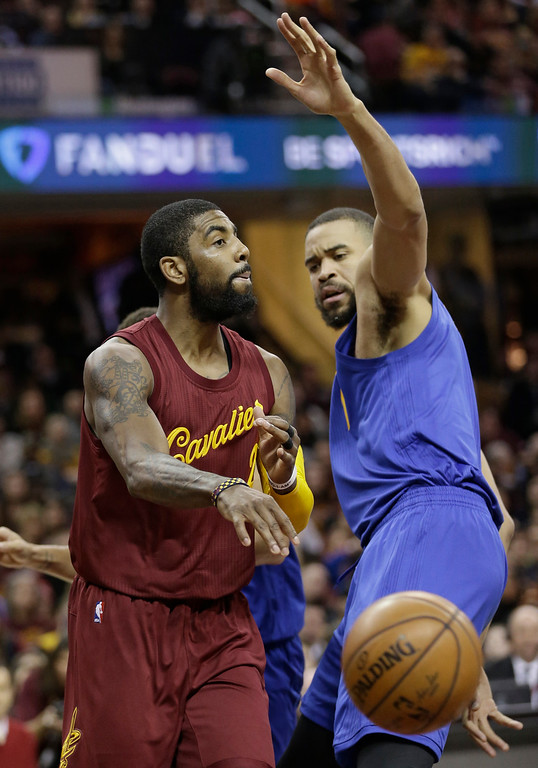 . Cleveland Cavaliers\' Kyrie Irving (2) passes around Golden State Warriors\' JaVale McGee (1) in the first half of an NBA basketball game, Sunday, Dec. 25, 2016, in Cleveland. (AP Photo/Tony Dejak)