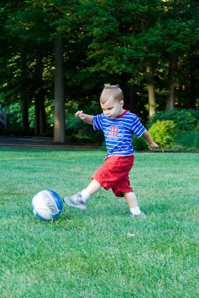 K.C. kicks a ball on the run.